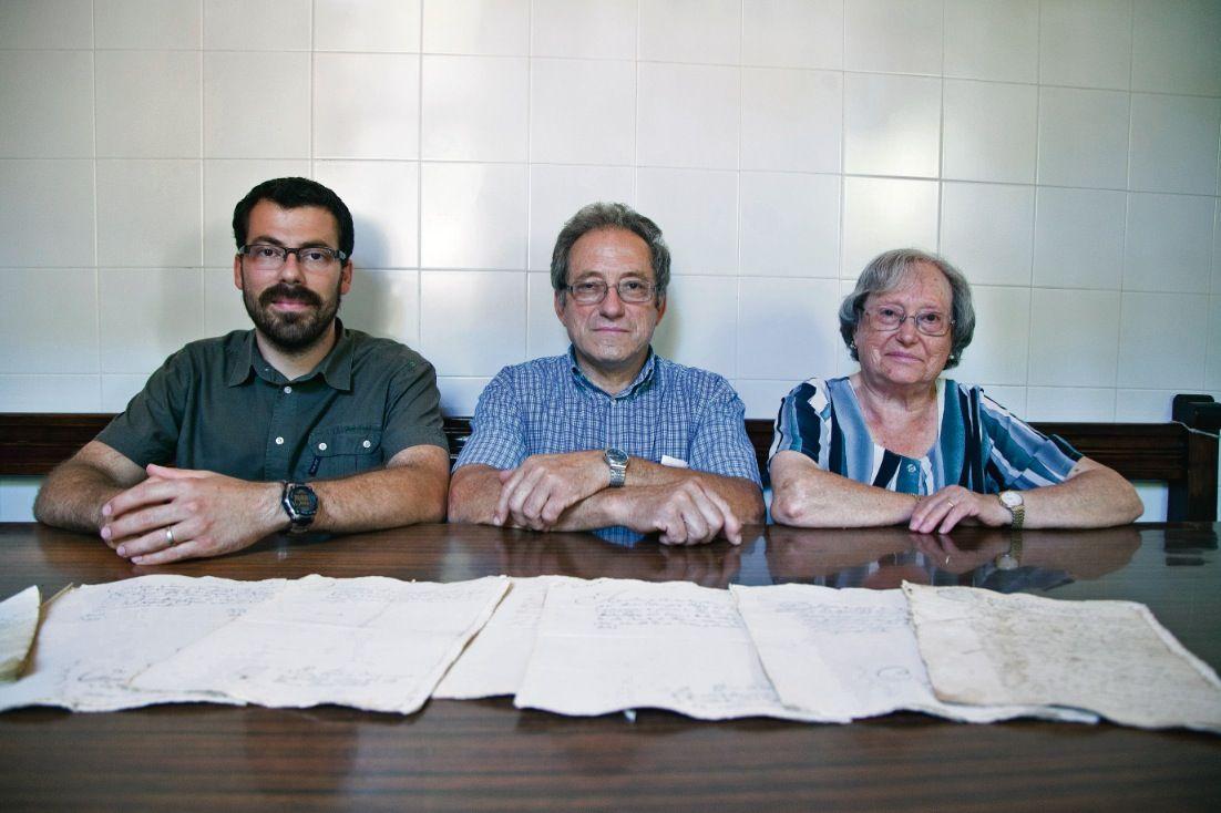 L'àvia Maria, el fill Gabino i el nét Isidre amb diversos documents antics de la masia. FOTO: Lali PUig