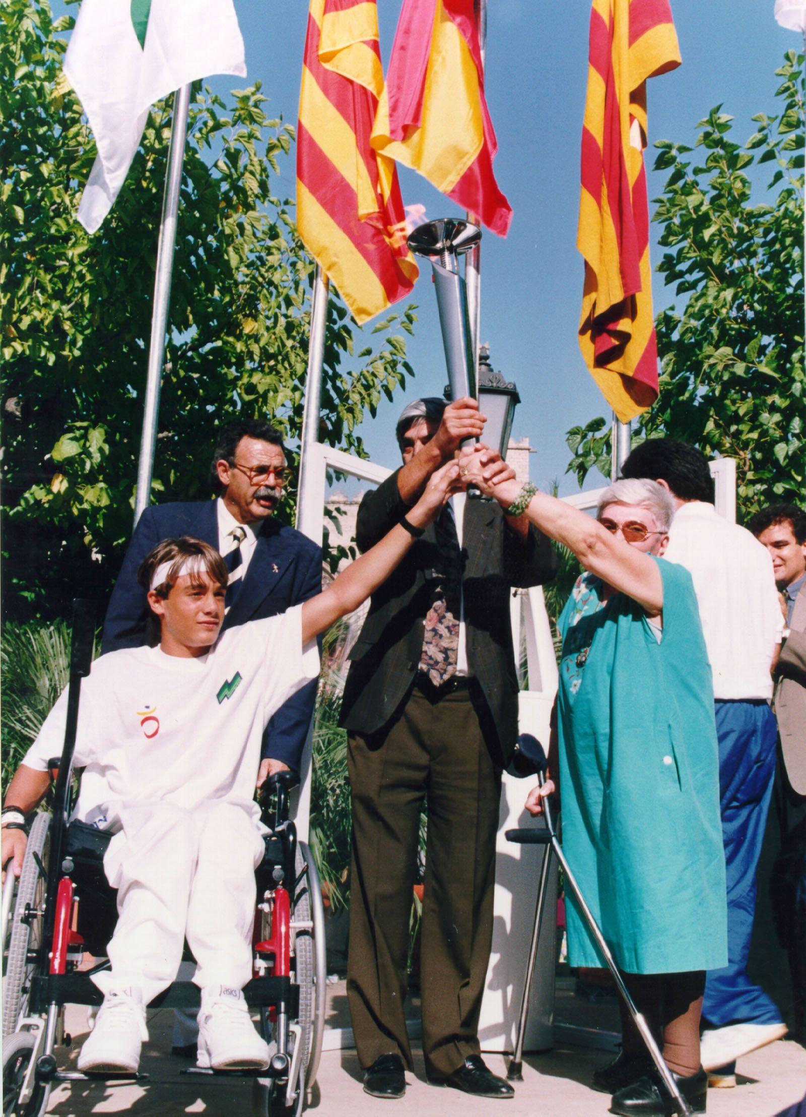 L'alcalde d'aleshores de Sant Cugat, Aymerich, aixeca la torxa dels Jocs Olímpics, juntament amb un esportista i  Pepa Llunell, incansable lluitadora contra les barreres arquitectòniques. FOTO: Cedida